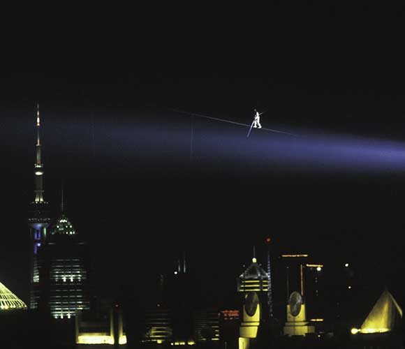 Jay Cochrane walks above the Pearl of the Orient Tower in Shanghai, China as he accomplished a world record for the highest and longest nighttime building-to-building wire walk on September 24, 1996 during the Shanghai Tourism Festival. ©Mark D Phillips