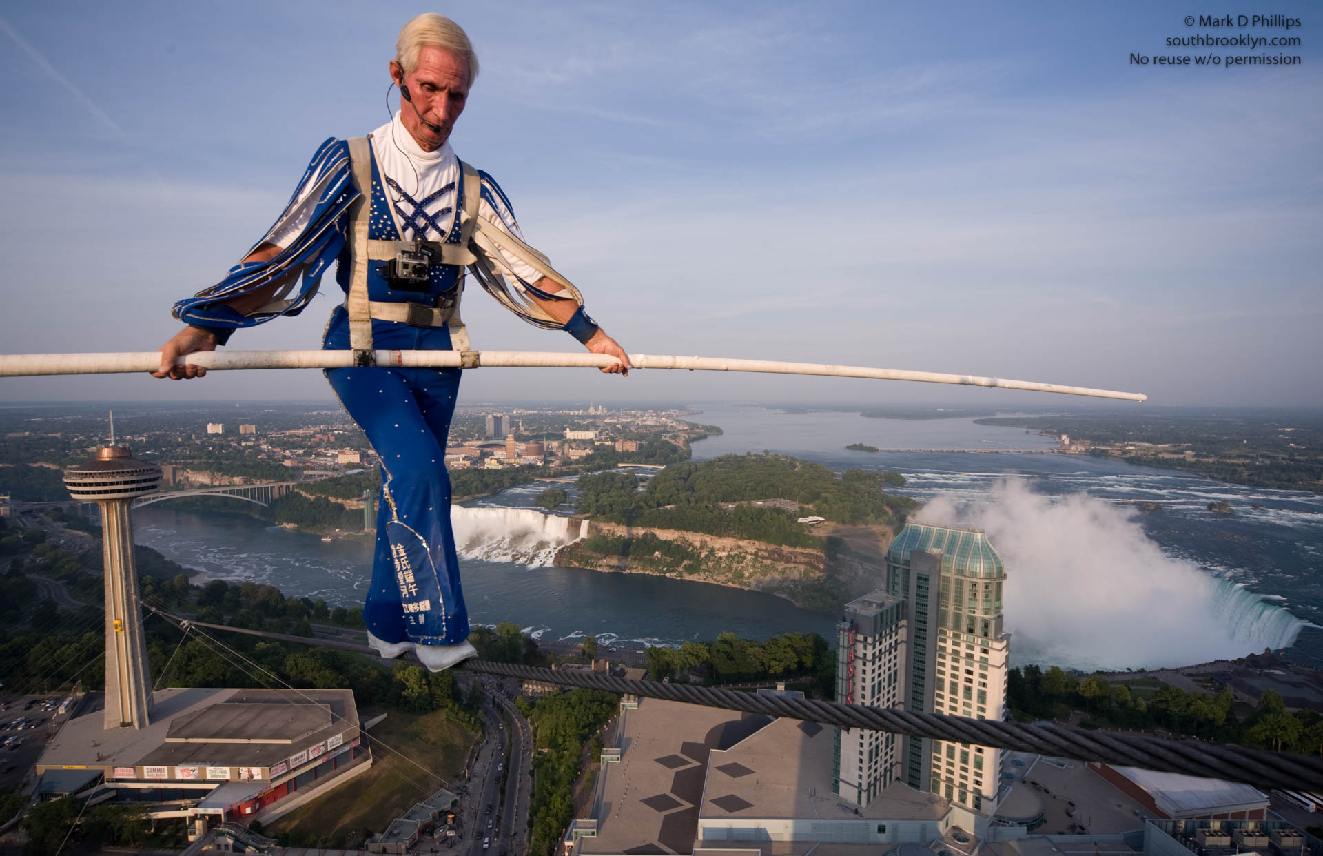 Jay Cochrane completes the first performance of Skywalk 2012, the Greatest Building to Building skywalk in North American history. Cochrane will grace the Niagara Falls skyline from the Skylon Tower (520 feet tall) to the top of the Hilton Hotel (581 feet tall) for the entire summer. At 1300 feet distance, he will cover approximately 20 miles on this wire in the 81 scheduled performances. ©Mark D Phillips
